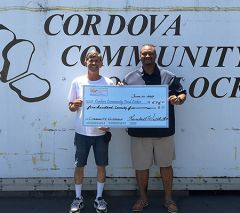 Cordova Community Food Locker Manager Gregg B. Huestis (left) receives a donation check from event planner Randall Wilhite (right).