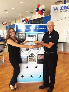 Larry Lane from Caliber Collision accepts a check from Stephanie Palombi of Folsom Lake Honda, one of many local Sacramento businesses who contributed towards Caliber Collision's 5th Annual Rhythm Restoration Food Drive to benefit Pacer Food Bank.  --Photo Courtesy of Caliber Collision