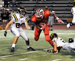 Cordova wide receiver Calvin Augusta slips past two Rio Linda players in last Friday's non-league football game at Lancers Stadium. The Lancers lost a tough one 31-29.  --Photo by Rick Sloan