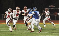 Cordova quarterback Xavier Johnson, 11, comes out of the pocket to pass while receiving protection from Deante McCullough, 21, Kelechi Njoku, 15 and Michael Gonzalez.  --Photo by Rick Sloan