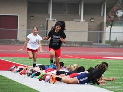 Members of the Cordova High School varsity girls soccer team take part in the centipede drill, where all girls laid down on the ground, except for one who leaps over the others and then drops at the end of the group.  --Photo by Mike Bush