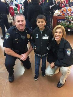 Officers from the Citrus Heights Police Department (above) are pictured with one happy young shopper at the 10th Annual Shop With A Cop event. 