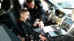 Nine year old Julian looks on with delight as Sgt.Wes Herman of the CHPD points out features on his police cruiser during the annual police Holiday Toy Drop-off on December 20. 
