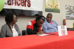 Kenny Haney, middle, signs his National Letter of Intent for Southern Oregon University last week at Cordova High School. Sitting with him are his parents Shelia, left, and Donald. Kenny becomes the first Cordova High School football player to sign with a four-year college in a decade.  --Photo by Mike Bush