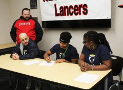 Elijah Morgera, middle, signs his National Letter of Intent in front of his parents, father Dean (left) and mother Erica, on the Cordova High School campus last week. Morgera, a two-sport athlete in football, plus track and field, has signed with Graceland University to play football. Standing on the side is Cordova track and field head coach Shane Jackson.  --Photo by Mike Bush