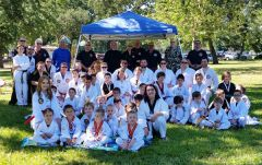 Students about to receive their new colored belts with the staff for Family Tai Know Do Plus and grand masters who will present the belts. 