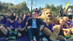 John Rinehart, Sacramento Kings president of business operations, huddles with kids and Kings' official mascot, Slamson the Lion, prior to the grand opening of the new Madera Park Basketball Court July 19. Photo by Jacqueline Fox