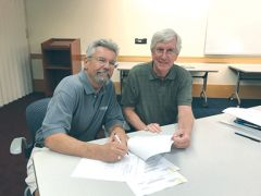 Hilary Gould (left), owner of Gould Electric and PBID Maintenance services signs the agreement with Gary Hursch. Photo by Linda Melody