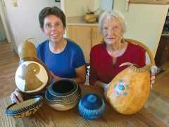 Colleen Ballard and Barbara Rippetoe show off some of the fine gourd art to be presented at the festival. Photo by MPG staff