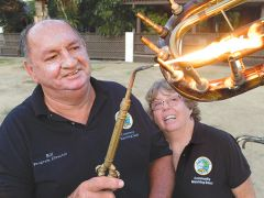 """Kathy Cook watches her husband, Bill Cook, use a brazing torch to connect the musical dinosaur's teeth.  After seeing a dinosaur made out of tubas on Facebook, Bill Cook decided to make a dinosaur to compliment the band's 2017 fanfare showpiece – the theme song from the """"Jurassic Park"""" movie.  Brassie, though, is made of 45 unusable trumpets, baritones, trombones, a clarinet, a flute, and a tuba. Photo courtesy CHMB"""