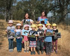 Guided by teachers Becky Page and Tavia Pagan, Orangevale kindergarten pupils enjoy an American River nature walk. The children display pictures of the rare bald eaglets they named Peekaboo and Poppy. Photo by Susan Maxwell Skinner