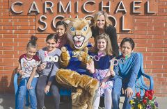 Carmichael Elementary Principal Brandei Smith (back right) and students join the school's cougar mascot. Cougar, alumni and current enrollees invite the community to celebrate the school's centenary on May 9.