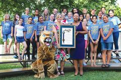 Principal Brandei Smith (left) joins incoming Principal Marianne Williams during celebrations for Carmichael Elementary School's 100th year. The educators hold a proclamation from Assemblyman Ken Cooley. School choir and cougar mascot joined festivities.