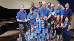 Tim's Music owner Scott Mandeville (center) and staff show the results of a food drive conducted in the Carmichael store. The donations assist local food banks.