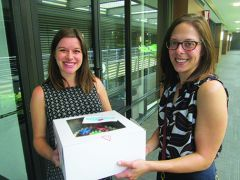 Alyssa Van Hofwegen (L) and Mary Barnes show off a delicious example of one of the cakes.