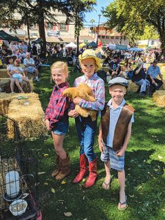 The winner of this year's Cluck n' Crow contest, Emily Rice (11), poses with her chicken Butterscotch, sister Annabelle (9), and brother Hudson (6).