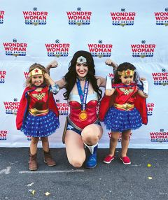 Wonder Woman poses with three-year-olds Roxy (left) and Isla (right).