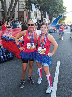 Jennifer Waldrop (left) and Allison Gove (right) show off their Wonder Woman medals after completing the 5K run with times of 29:42 and 29:44, respectively.