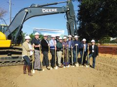 Management and development staff team up to launch the groundbreaking with the first dig. Photo by Paul Scholl