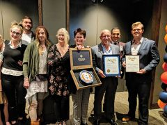 """Kathilynn Carpenter, recipient of Stone's third annual """"21"""" Award with members of her family on her left, and Stone's Kermit Schayltz, General Manager Art Van Loon, and District Representative for Senator Jim Nielsen, Landon Wolf on her right."""