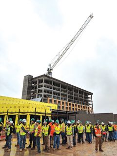 The workers who constructed the building from the ground up wait to see the final beam set atop the structure.