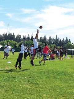 A player jumps into the air to catch a long pass. Photo by Shaunna Boyd