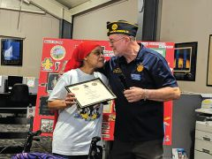 Michael Hughes, Adjutant of Lenard Yates American Legion Post 709, presents a certificate of recognition to Valerie Yates, in honor of her father's many years of service.