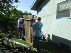 Two volunteers begin to replace yard fencing during the Rebuilding Together event.