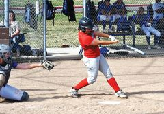 Kalyssa Fortier of the Lady Lancers Varsity Softball makes a base hit. Photo by Rick Sloan