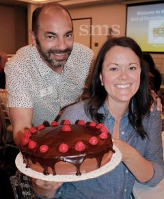 Chamber director John Foderaro tempted bidders with a chocolate and raspberry cake donated by Heidi Green (right).