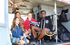 A group of students aboard a Bell UH1H utility military helicopter at Mather Airport. Photograph by Steve Burke Photography