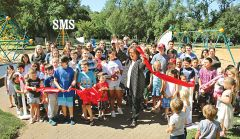 County Supervisor Susan Peters and Angeline Lara (12) shared ribbon-cutting honors at Carmichael Park's new children's playground.
