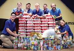 Tim's Music owner Scott Mandeville (back, center) and staff show the results of a food drive conducted in their Carmichael store. Donations assist local food banks.
