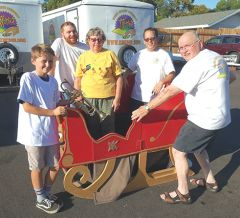Band members ready Santa's sled for the Howl 'o Ween parade. As is his annual tradition, Santa will be Grand Marshal of the parade and then will meet with Festival attendees. Pictured are Blake Heidt (left), Ryan Watson, Kathy Cook, Joe Isaacs, and Harold Huff. The guys are members of CHCMB's trumpet section and Cook is the band's Program Director. Photo courtesy of Citrus Heights Community Marching Band