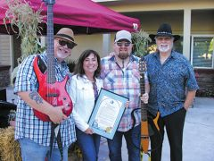 Randi Beasley of Summerset Senior Living was delighted to show the City's Proclamation with country music band Big Trouble's bass player Dan Cribb (left), guitarist Gary Blodgett and pedal steel guitar player Tom Phelps (right). Photo by Patrick Larenas