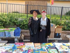 Neilu Golshanara of the Fair Oaks Rotary Club (left) and volunteer Oliver Glancy (right) distribute free books to costumed kids at the annual Safe Halloween event in Fair Oaks Village.